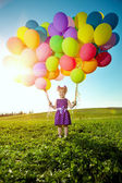 Happy little girl holding colorful balloons. Child playing on a — Stock Photo