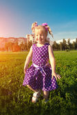 Beautiful little girl on the grass in the park. Smiling child on — Stock Photo