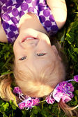 Cute little girl lying on the grass in the park. Smiling nice ch — Stockfoto