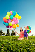 Beautiful little girl with mother colored balloons and rainbow u — Stock Photo