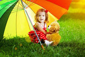 Happy little girl with a rainbow umbrella in park. Child playing — Stock Photo