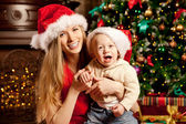 Happy smiling family near the Christmas tree celebrate New Year. — Stockfoto