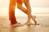 A loving young couple hugging and kissing on the beach at sunset — ストック写真