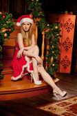 Young beautiful smiling santa woman near the Christmas tree. Fas — Stock Photo