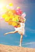 Beautiful young stylish woman with multi-colored rainbow balloon — Stock Photo