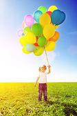 Liten flicka anläggning färgglada ballonger. barn som leker på en grön — Stockfoto