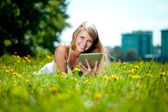 Beautiful smiling woman with tablet pc, outdoors. Beautiful youn — Stock Photo