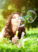 Woman and soap bubbles in park. Beautiful young girl lying on th — Stock Photo