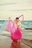 在他的手在海滩上纸巾的女人 — 图库照片