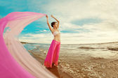 Woman with a tissue in his hands on the beach — Stock Photo