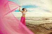 Vrouw met een tissue in zijn handen op het strand — Stockfoto