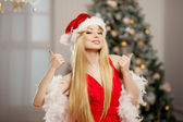 Young beauty santa woman near the Christmas tree. Fashionable lu — Stok fotoğraf