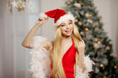 Young beauty santa woman near the Christmas tree. Fashionable lu — Stock Photo