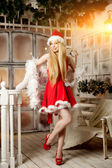 Young beauty santa woman near the Christmas tree. Fashionable lu — Stock fotografie