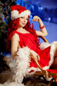 Young beauty smiling santa woman near Christmas tree. Fashionabl — Zdjęcie stockowe