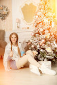Beautiful young woman drinking tea at the Christmas tree. Beauti — Stock Photo