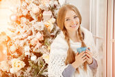 Beautiful young woman drinking tea at the Christmas tree. Beauti — Stock Photo