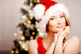 Young beautiful smiling santa woman near the Christmas tree. Fas — Stok fotoğraf