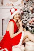 Young beauty smiling santa woman near the Christmas tree. Fashio — Stock Photo