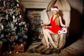 Young beauty smiling santa woman near the Christmas tree. Fashio — Stok fotoğraf