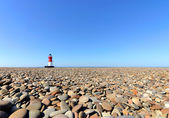 Lighthouse with Beach Pebbles in foreground — Stock Photo