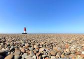 Phare avec plage de galets au premier plan — Photo
