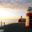 Lighthouses on breakwater wall with calm sea during sunrise — Stock Photo #42184155