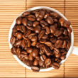 Full cup with coffee beans on the table — Stock Photo #14023442