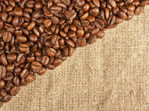Many coffee beans on coarse fabric — Stock Photo