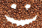 Smiling face on the background of coffee beans — Stock Photo