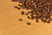 Many coffee beans on wooden table — Stock Photo