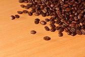 Kupie palonych ziaren kawy na drewnianym stołem — Zdjęcie stockowe