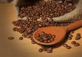 Grains de café torréfiés dans un sac avec une cuillère en bois — Photo