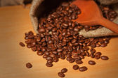 Pile of coffee beans in a sack and wooden spoon — Stockfoto