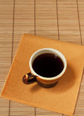 One cup of coffee on a yellow napkin — Stock Photo