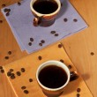 Two cups of coffee on napkins with coffee beans - Stock Photo