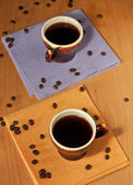 Two cups of coffee on napkins with coffee beans — Stock Photo