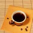 Foto Stock: One cup of coffee with coffee beans on table