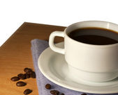 White cup of coffee on a saucer closeup — Stock Photo