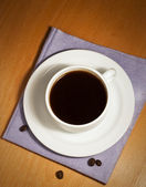 White coffee cup and saucer on a napkin — Stock Photo