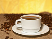 A cup of coffee on burlap on the table — Stock Photo