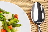 Sliced vegetables on a plate and spoon — Stock Photo
