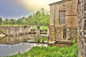 Old ruined mill on the river — Stockfoto