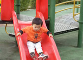 Baby playing on sliding board — Stock Photo