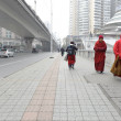 Tibetan monk dressed in red frock walking on urban road — Stok fotoğraf