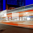 Photo: High speed and blurred bus light trails in downtown nightscape