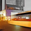 High speed and blurred bus light trails in downtown nightscape - Lizenzfreies Foto