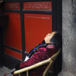 Tired old woman sleeping on a chair in the temple — Stock Photo