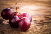 Red grape on wooden table, closeup — Stock Photo