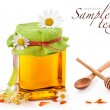Honey in glass jar and wooden honey dipper - Stock Photo